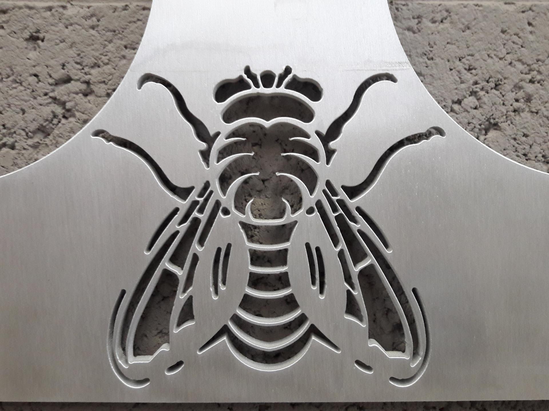 Zoom sur une mouche découpée dans de l'aluminium.